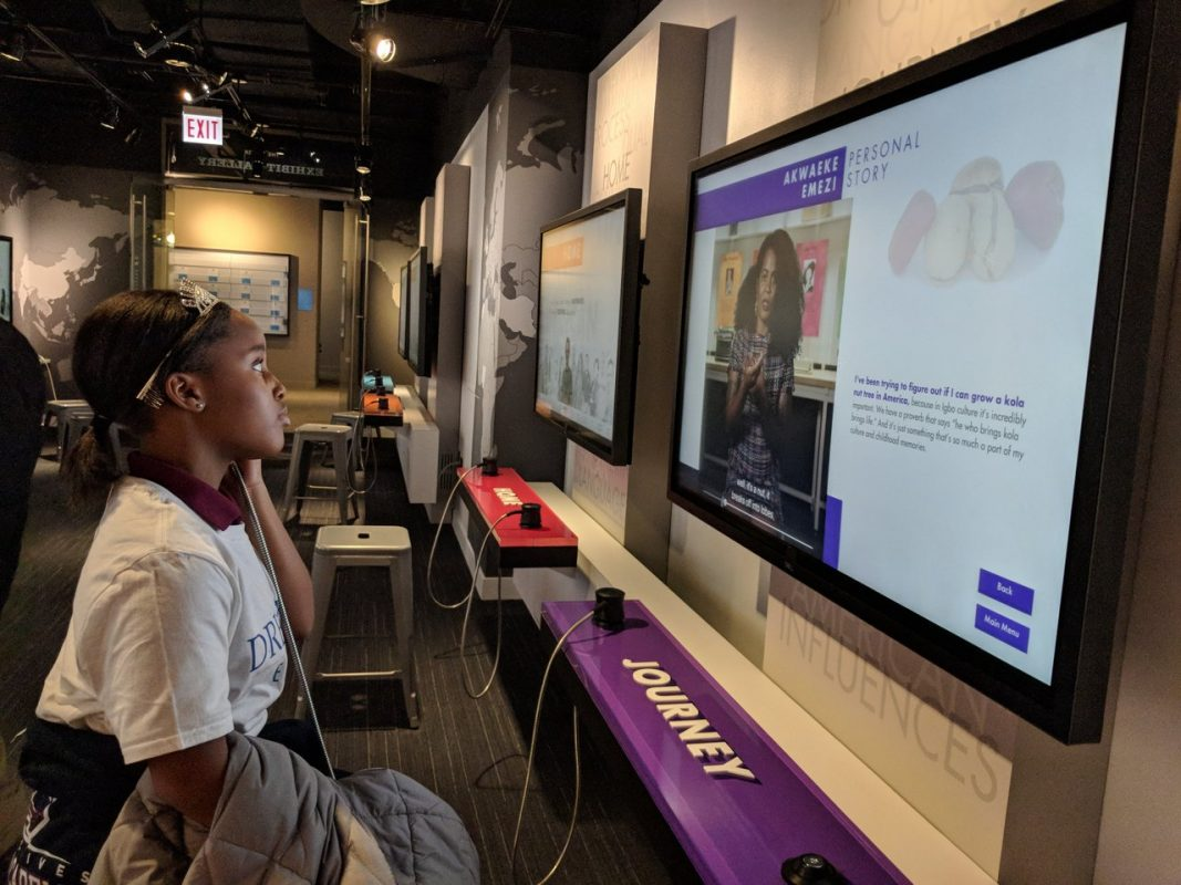 "A student listening to an interview with Vu Tran at one of the ""Journey"" monitor in My America: Immigrant and Refugee Writers Today at the American Writers Museum in Chicago"